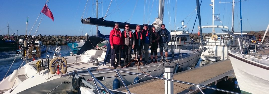 Group of 6 people standing on a yacht chartered from Go West Sailing Scotland